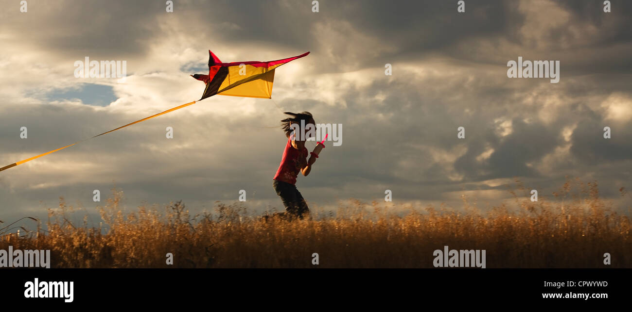 A panorama of a girl happily flying her kite. - Stock Image