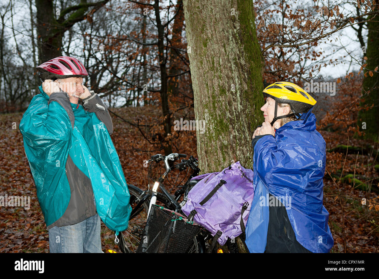 Senior couple preparing to cycle in forest - Stock Image