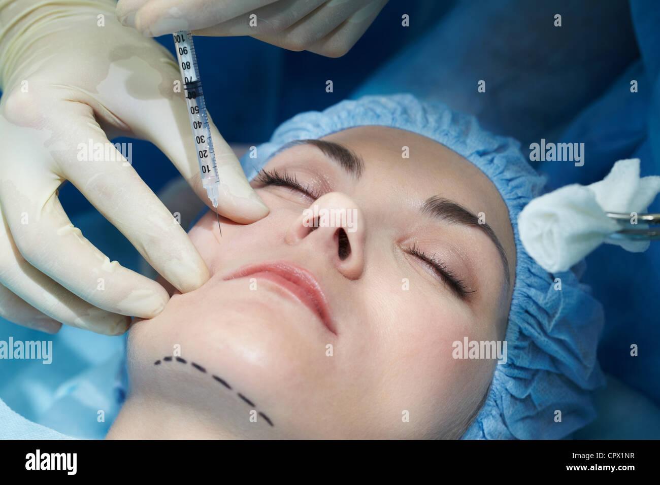 Young woman having facial plastic surgery - Stock Image