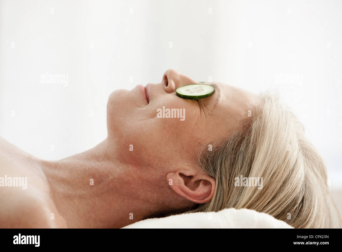 Mature woman relaxing with cucumber slices over eyes Stock Photo