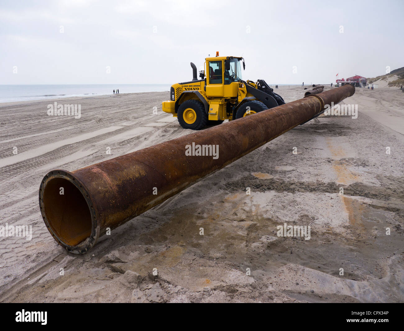 Dredger moves pipe / tube for hydraulic filling of sand on a Dutch North Sea beach (to prevent coastal erosion) - Stock Image