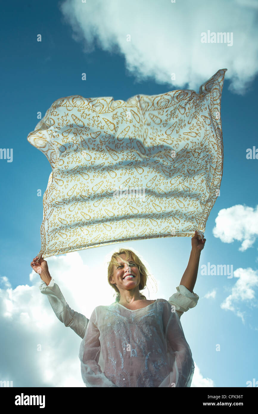 Person holding sarong in breeze over woman's head - Stock Image