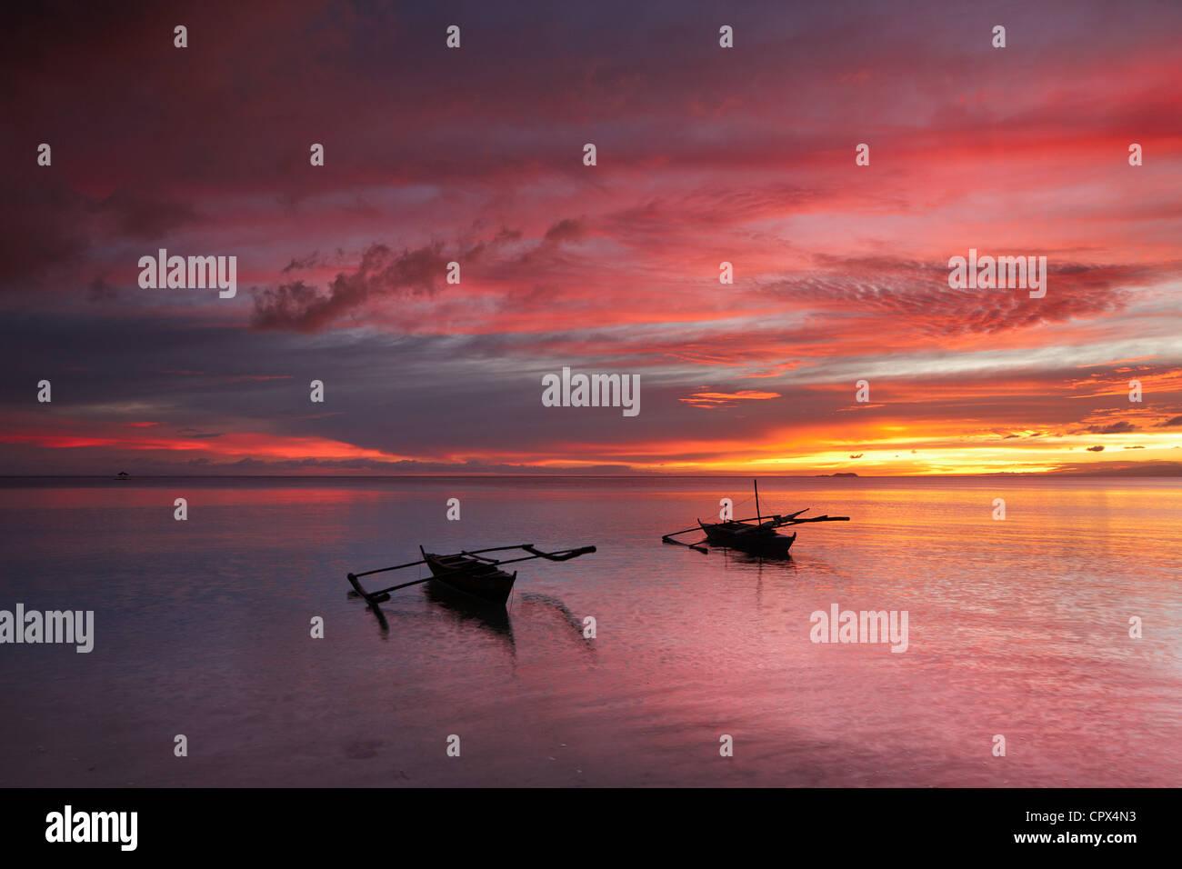 two boats off San Juan Beach at dusk, Siquijor, The Visayas, Philippines - Stock Image