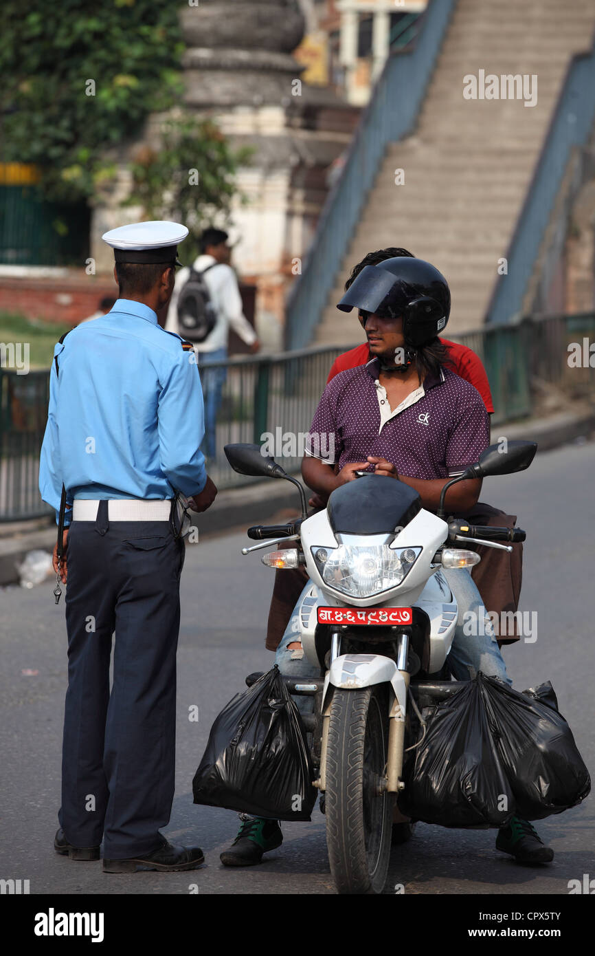 Police officer controlling a motorbike Nepal - Stock Image