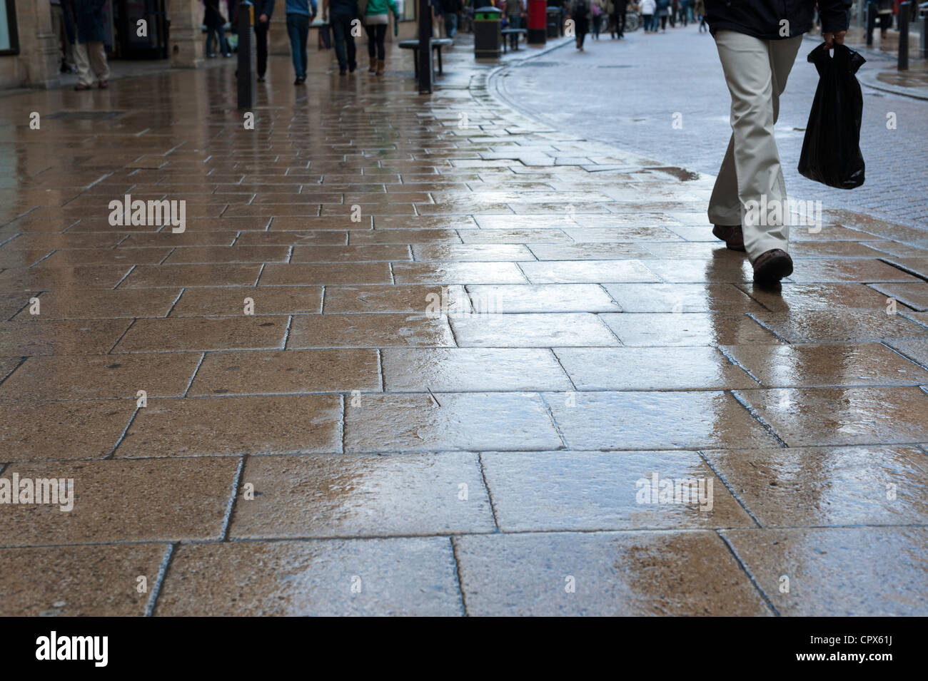A wet pavement reflecting light on a raining day in Cambridge UK with legs and feet of people walking by. - Stock Image