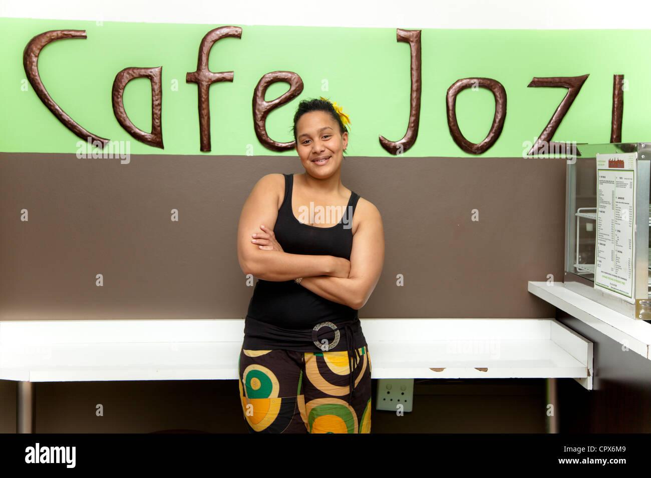 Girl in café smiles at camera - Stock Image