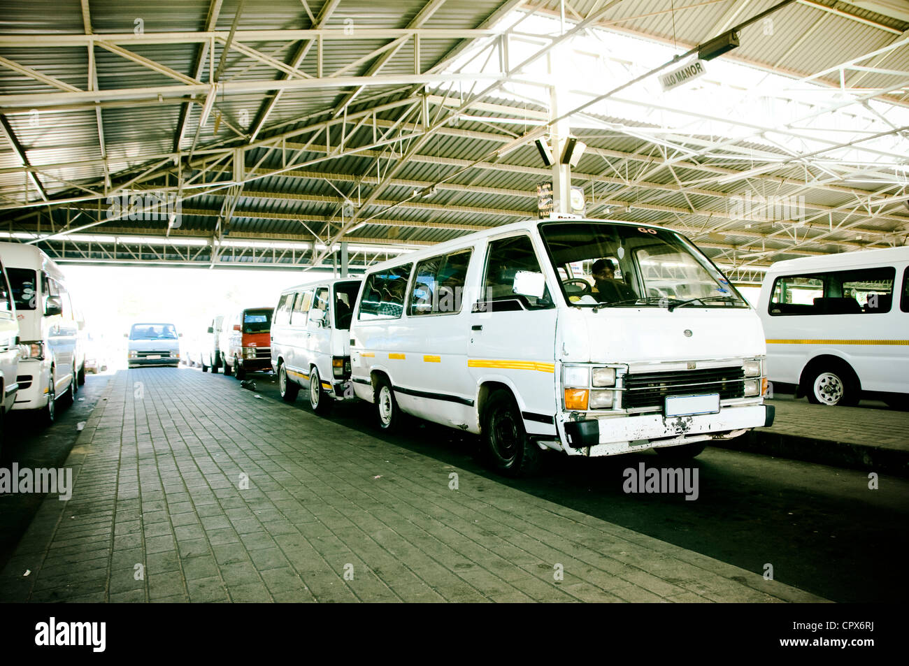 Minibus taxis parked inside a taxi rank - Stock Image