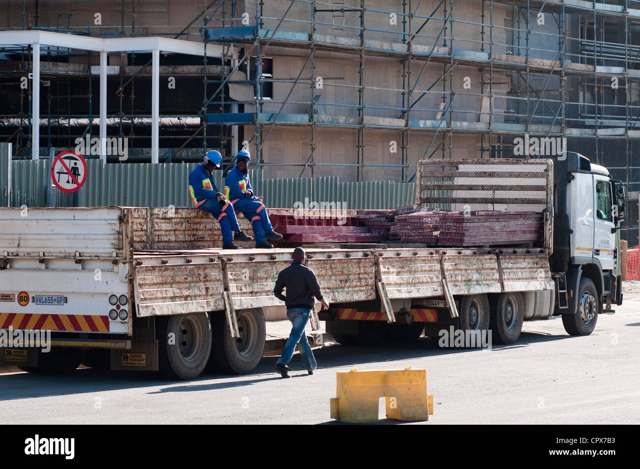 Construction workers sitting on a construction vehicle, Sandton - Stock Image