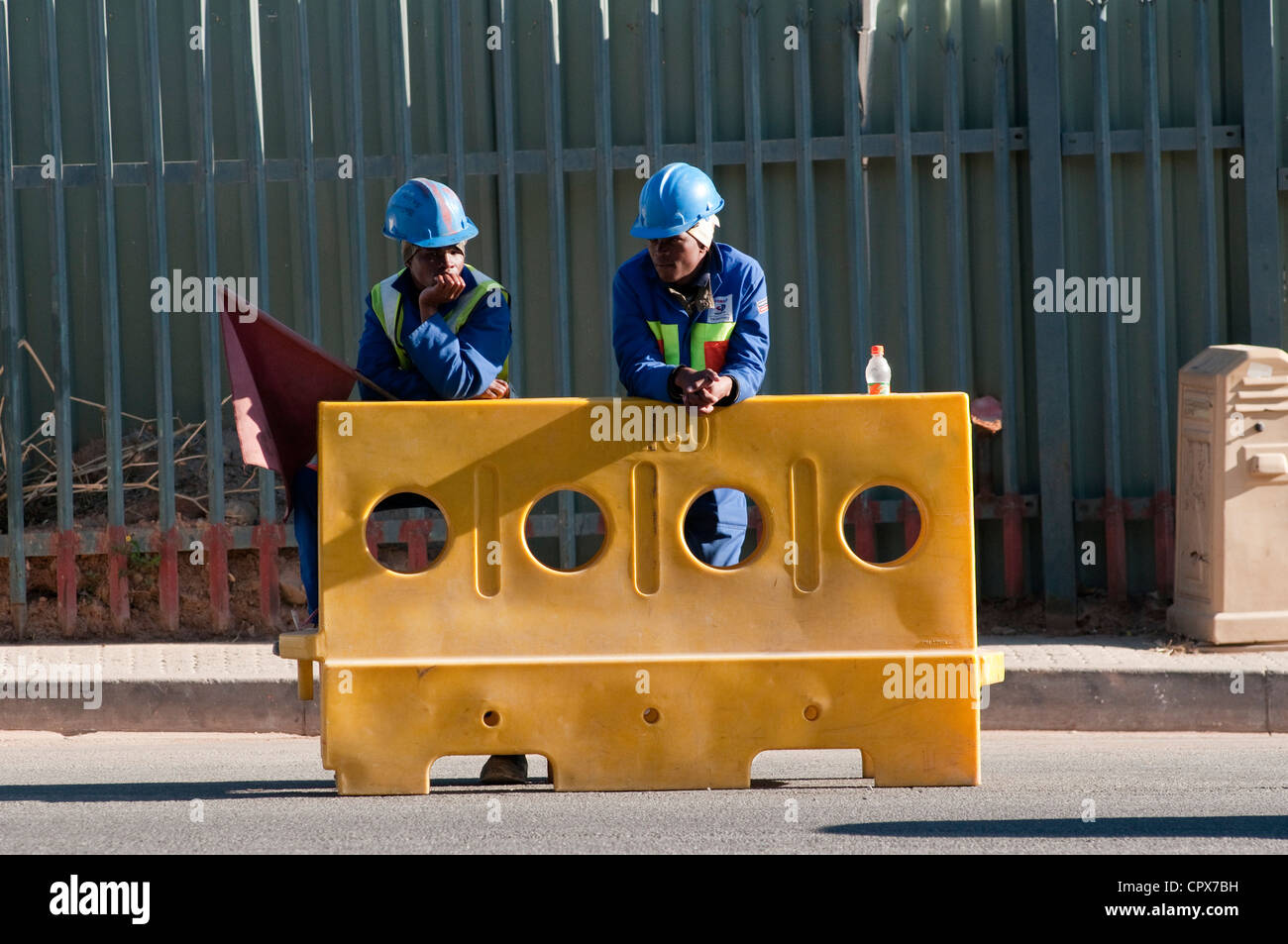 Two construction workers standing next to a traffic barrier - Stock Image