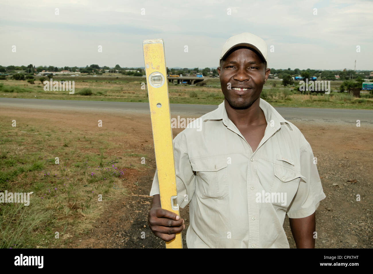 Black construction worker posing with spirit level - Stock Image