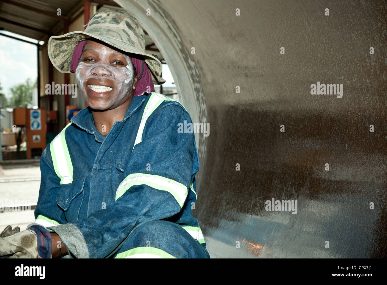 Black female factory worker cleans the inside of a large pipe, smiling - Stock Image