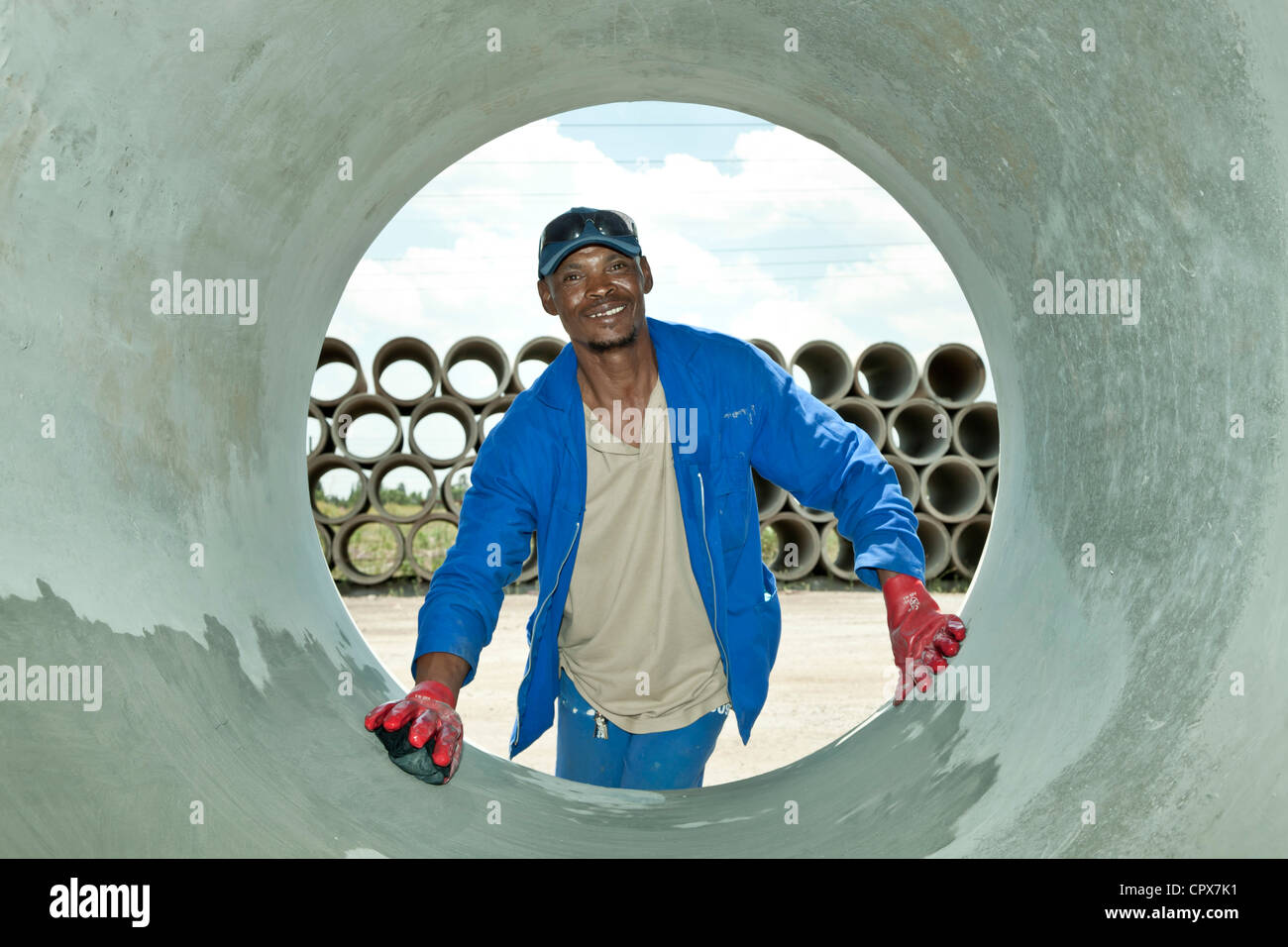 Black construction worker cleans the inside of a large pipe - Stock Image