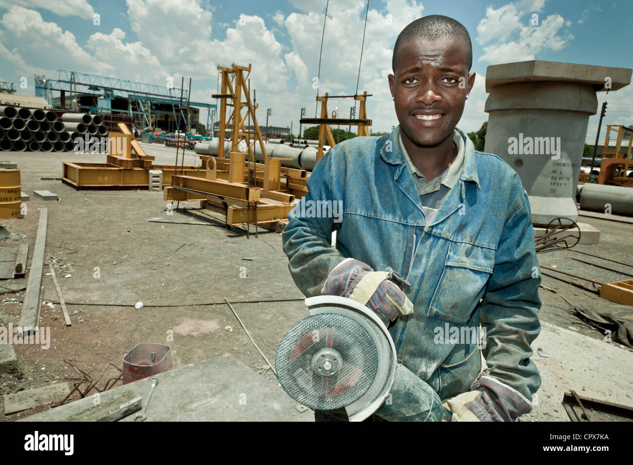 Black construction worker holds an angle-grinder and smiles at camera - Stock Image