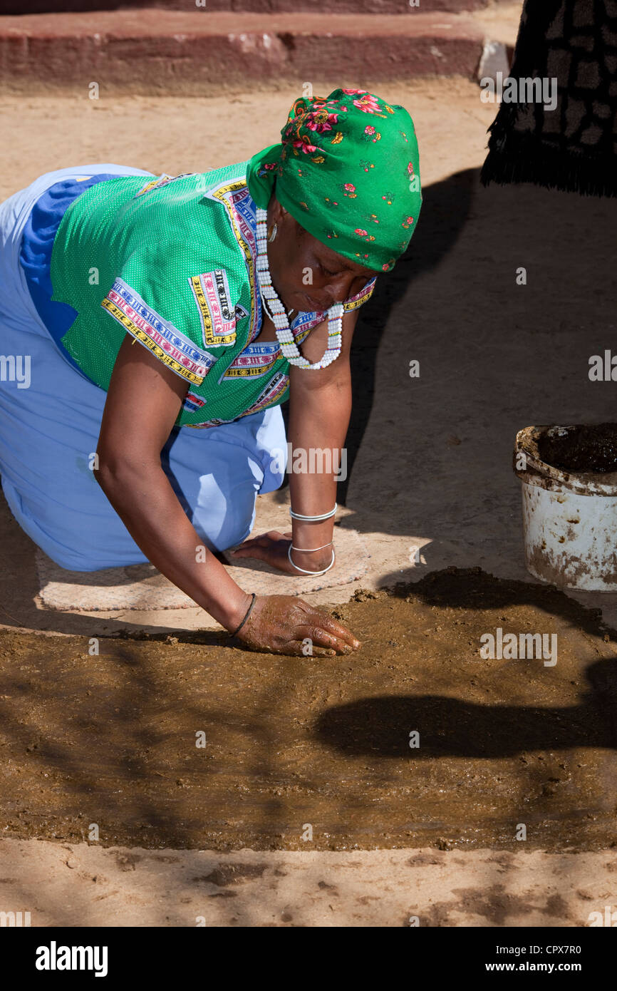 Traditional African woman spreading mud and clay on the floor - Stock Image