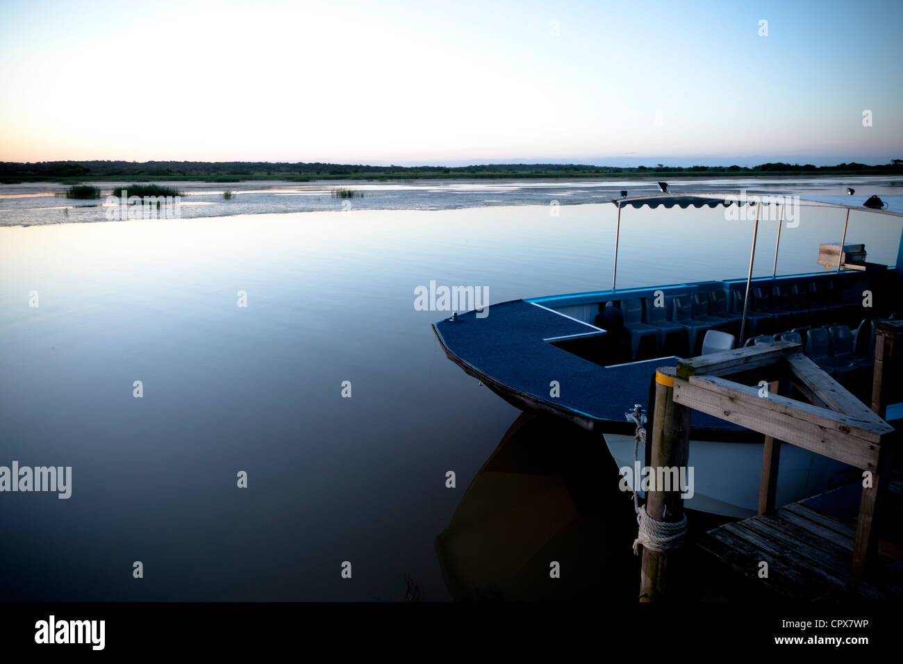 Overall view of a dam at dawn, with a boat in the foreground - Stock Image