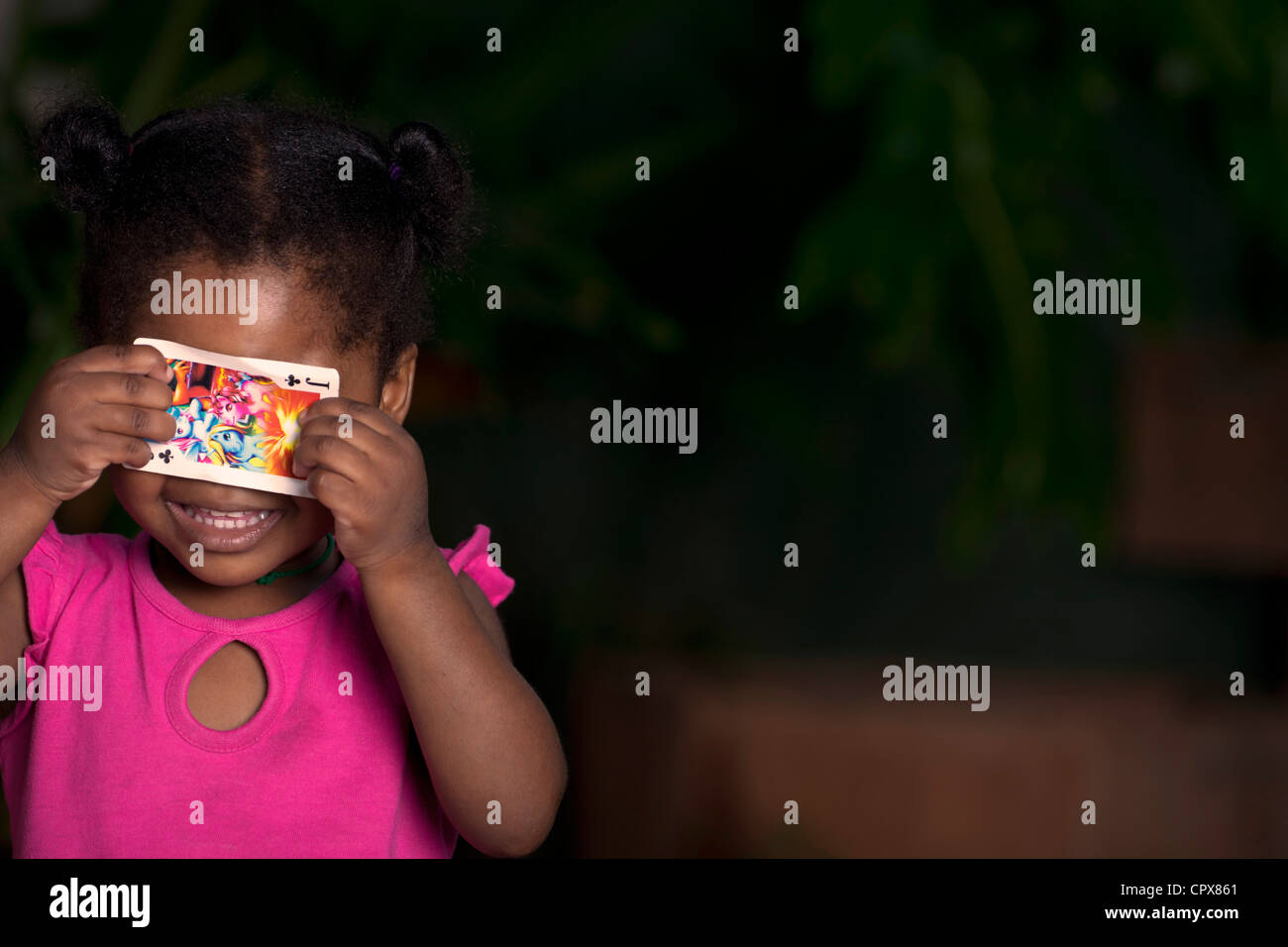 Young female black child holding a playing card over her eyes - Stock Image