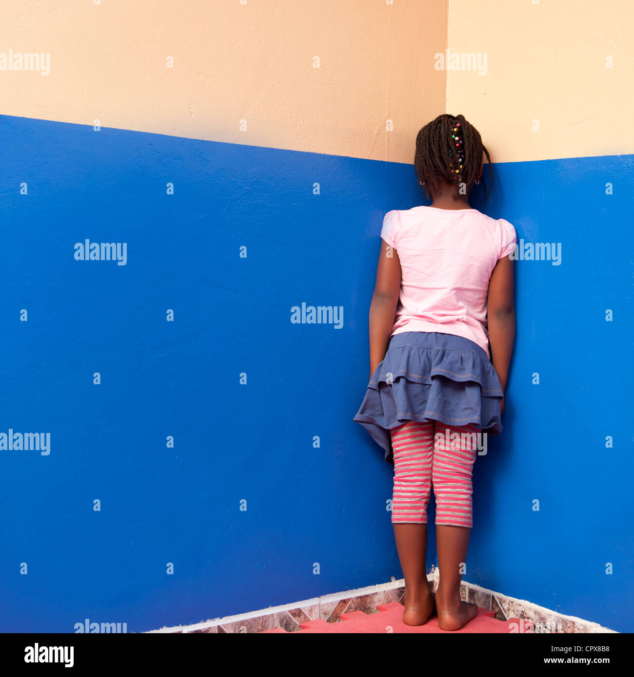 Standing In The Corner : Child standing in the corner facing wall stock photo