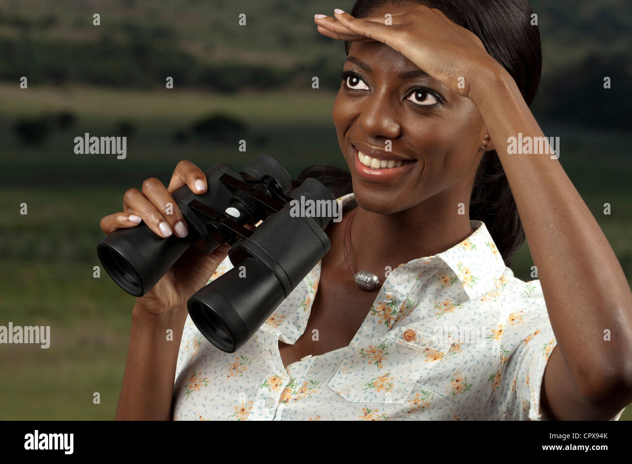 An African woman searches for game while holding binoculars - Stock Image