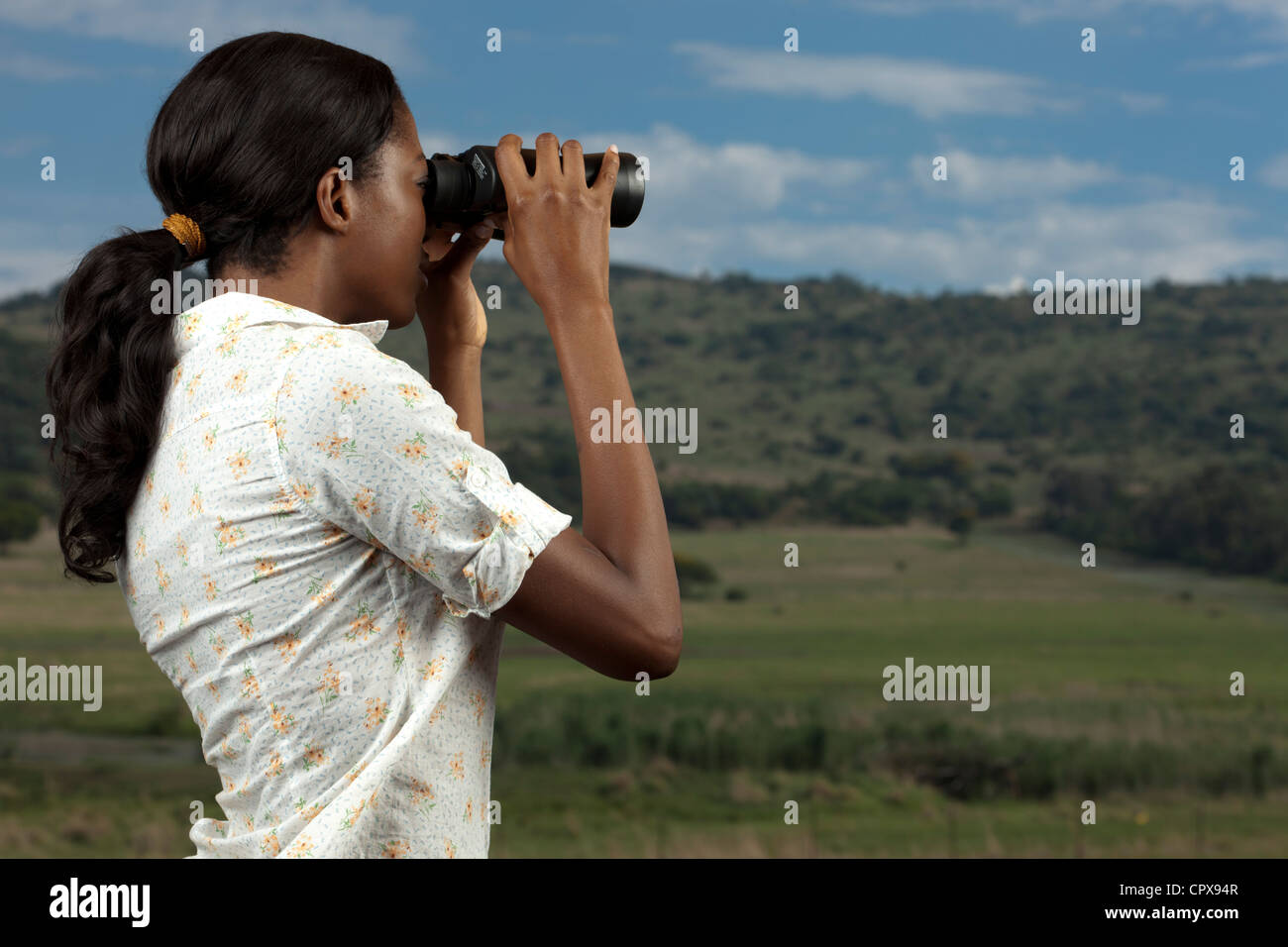 An African woman searches for animals at a Game Reserve through binoculars - Stock Image