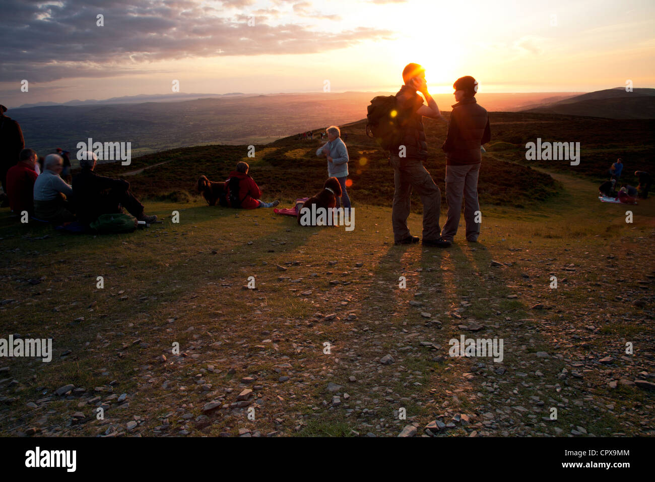 Hill walkers at Moel Famau the highest peak in the Clwydian Range at sunset enjoying the landscape and view of vale - Stock Image