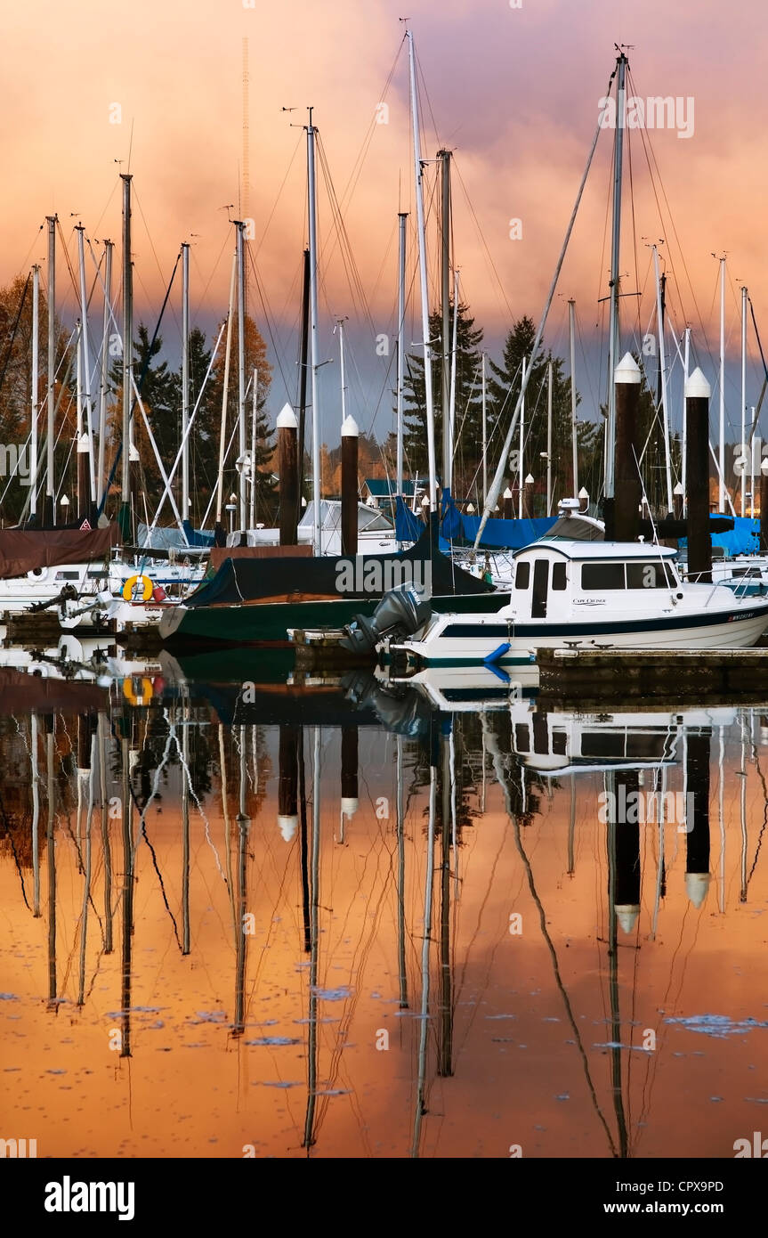 A glorious sunrise sky is reflected in the water at the Swantown Marina in Olympia, Washington. - Stock Image