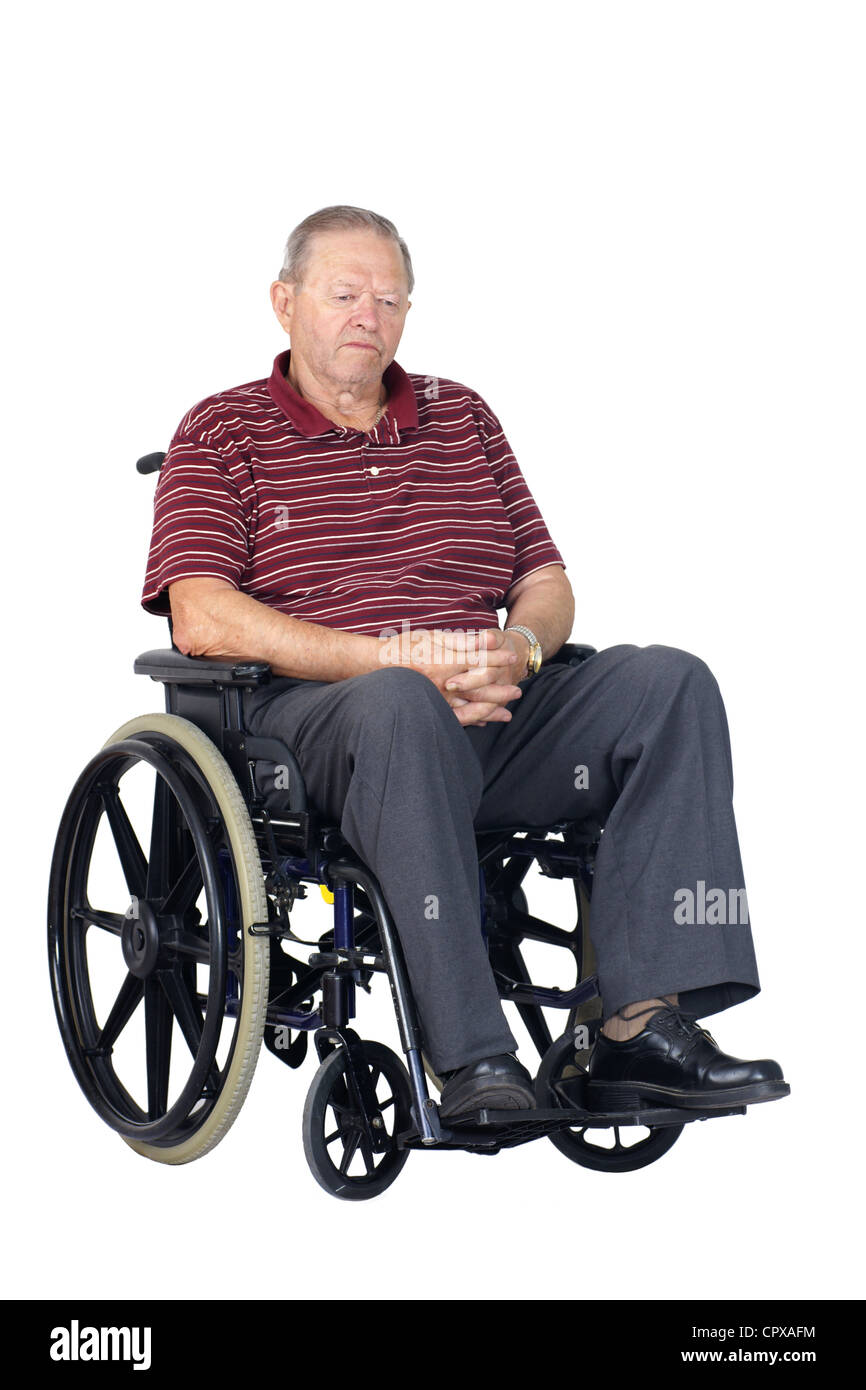 Sad or depressed senior man in a wheelchair, looking down, studio shot isolated over white background. - Stock Image