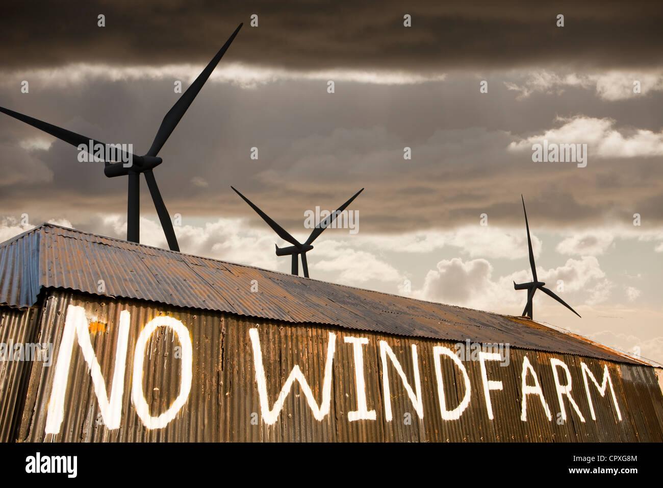 composite of a wind farm and an anti wind farm protest on a barn outside Carlisle, Cumbria, UK. - Stock Image
