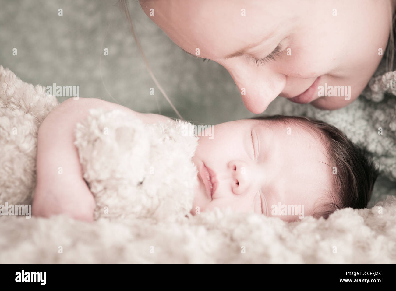mother leans over newborn baby to kiss - Stock Image
