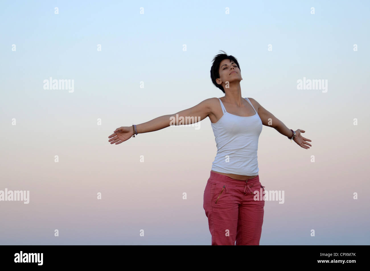 Attractive young woman relaxes in nature with arms wide open - Stock Image