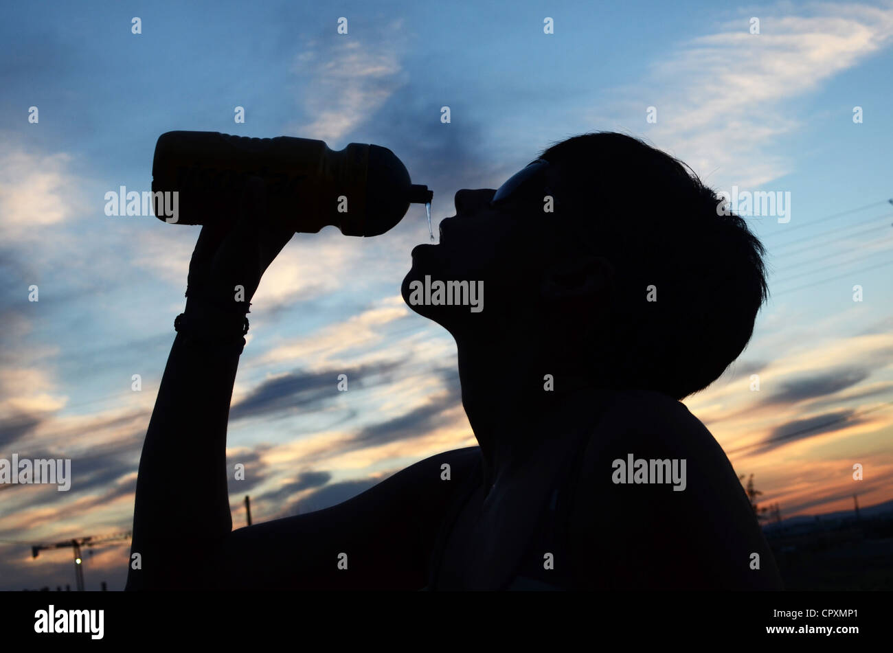 Young woman drinks water after bike ride Stock Photo