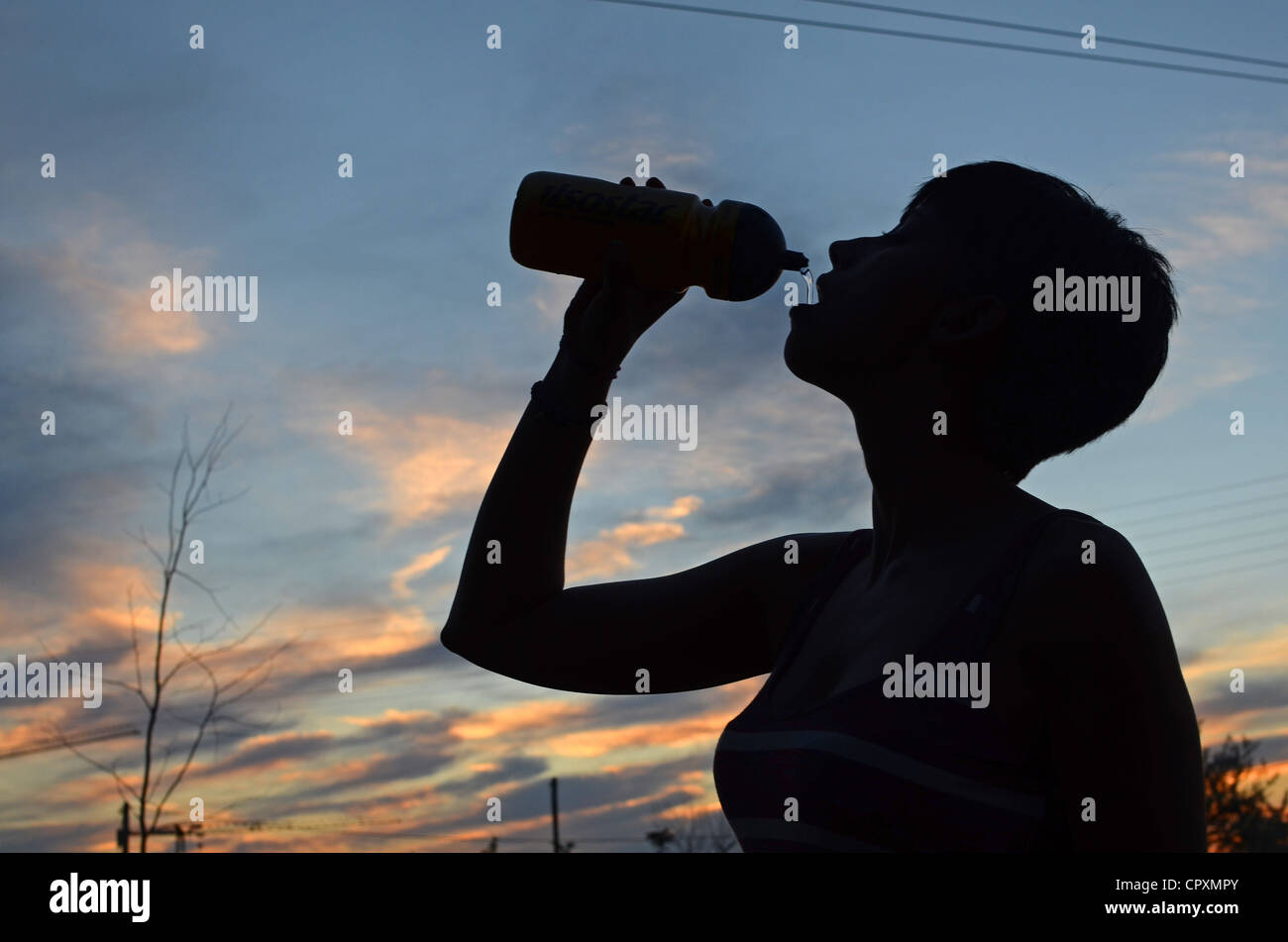 Young woman drinks water after bike ride - Stock Image