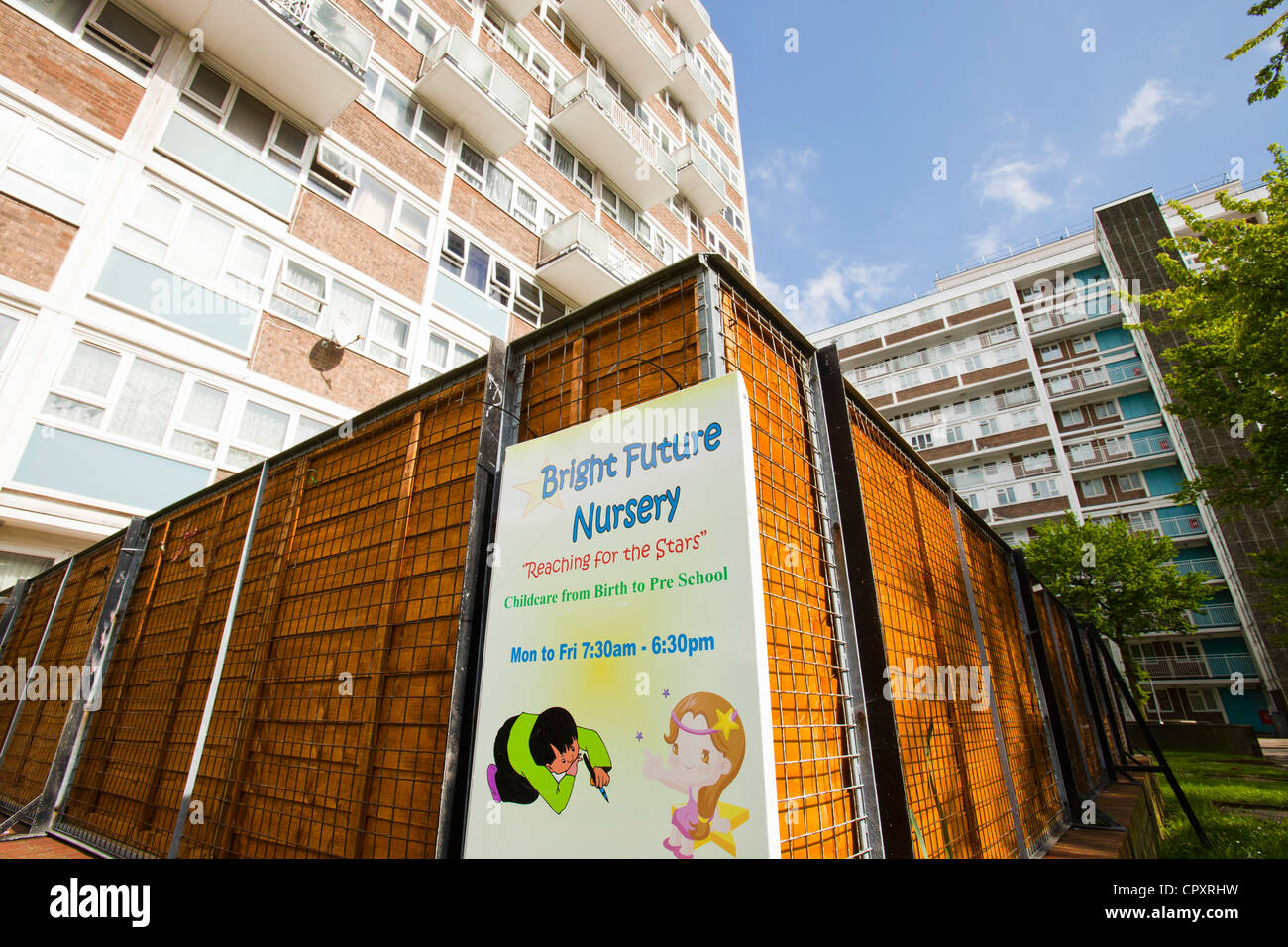 A child nursery by run down council flats in Queens Park, London, UK. - Stock Image
