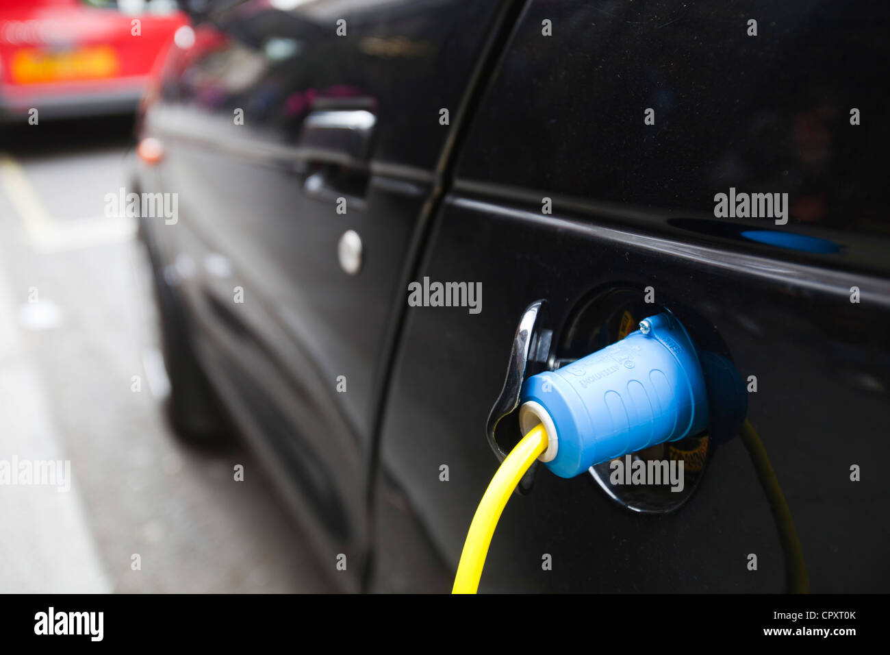 An electric vehicle at a recharging station on the street in Berkeley Square, London, UK. - Stock Image