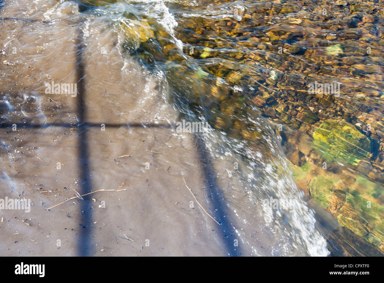 Raw sewage mixing with clean clear water in the river Kent in Kendal, Cumbria, UK. - Stock Image