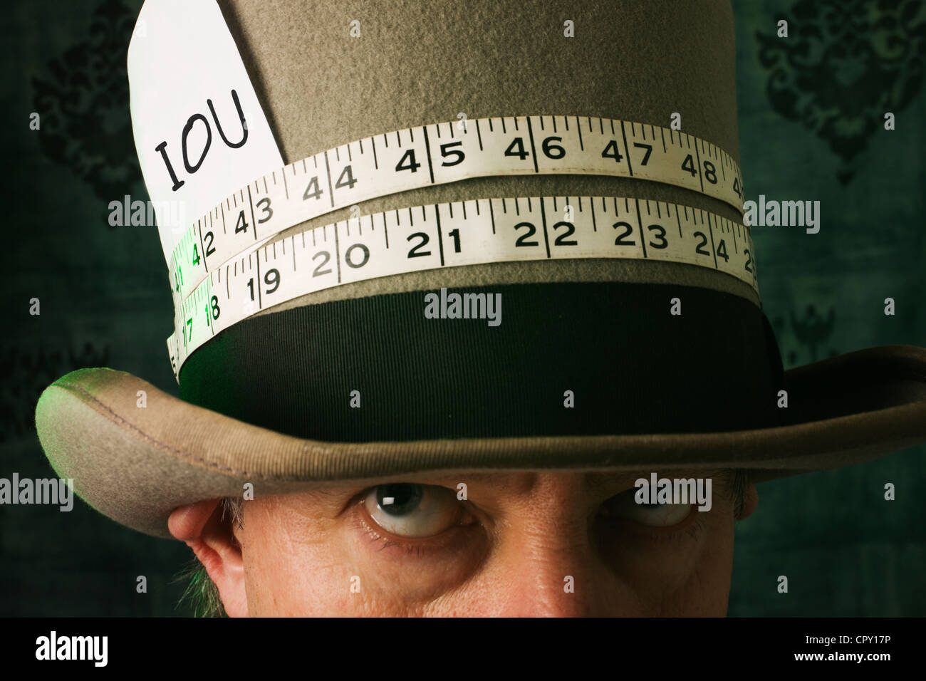 A mad hatter like man looking up at the IOU on his hat. - Stock Image