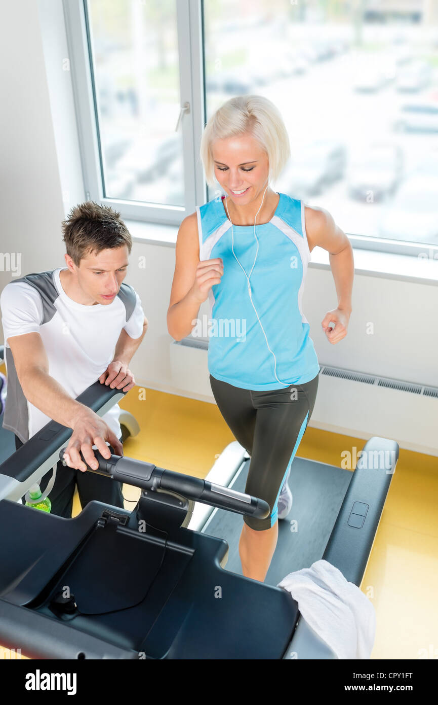 Young personal trainer instruct woman running at fitness center - Stock Image