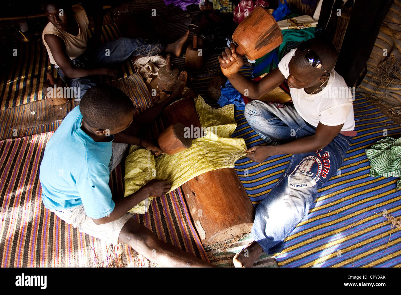 Mali, Bamako, Bazin cloth is hit during long minutes to become shiny and to fix the color - Stock Image