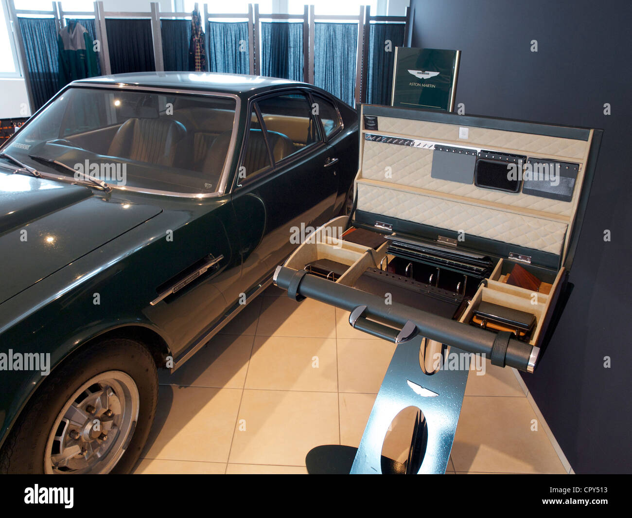 Classic Aston Martin DBS V8 sportscar at dealership with special suitcase showing some refurbishment options - Stock Image