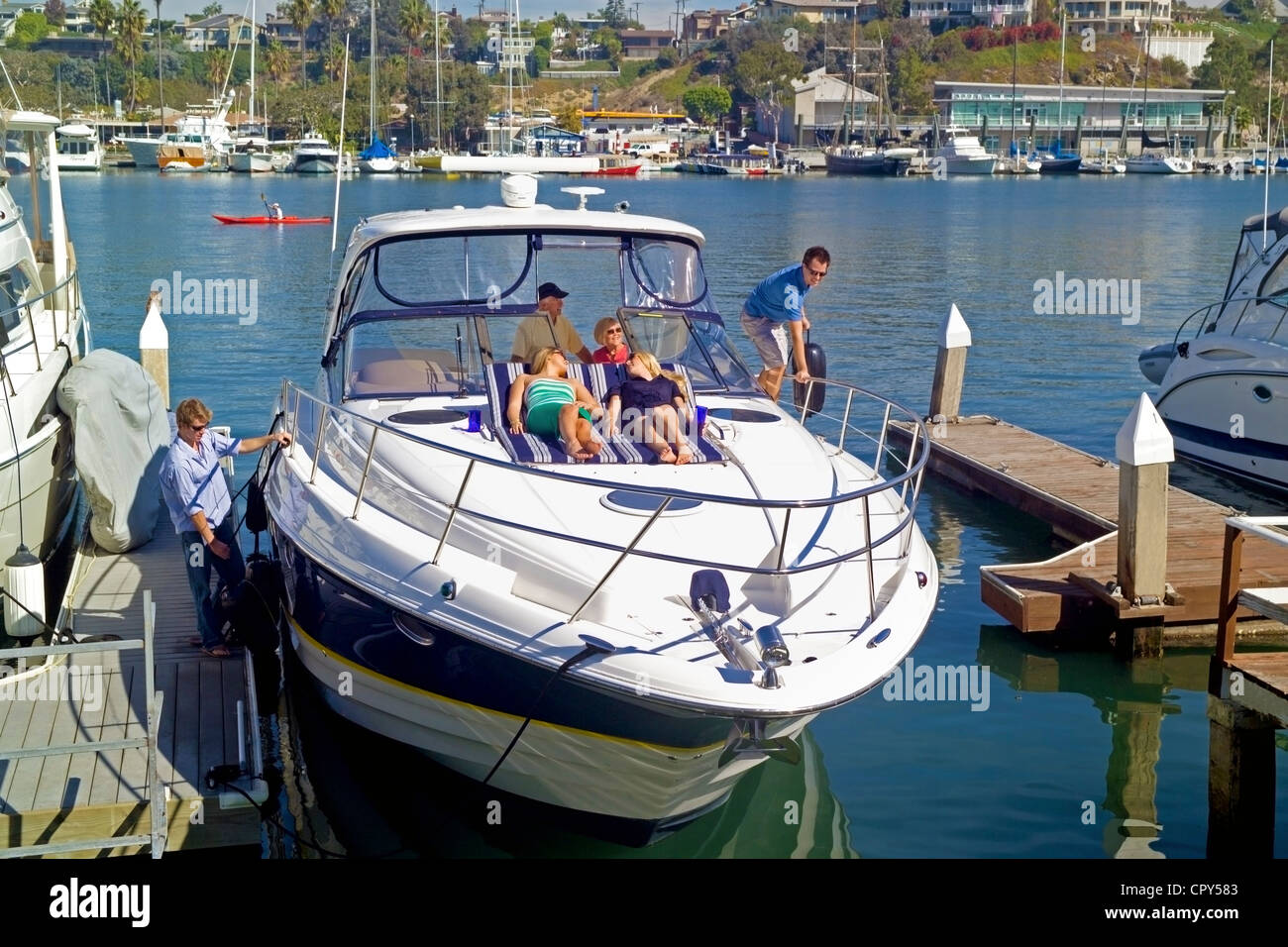A yachting family and their friends cast off from their private Lido Isle dock for a cruise into the Pacific Ocean - Stock Image