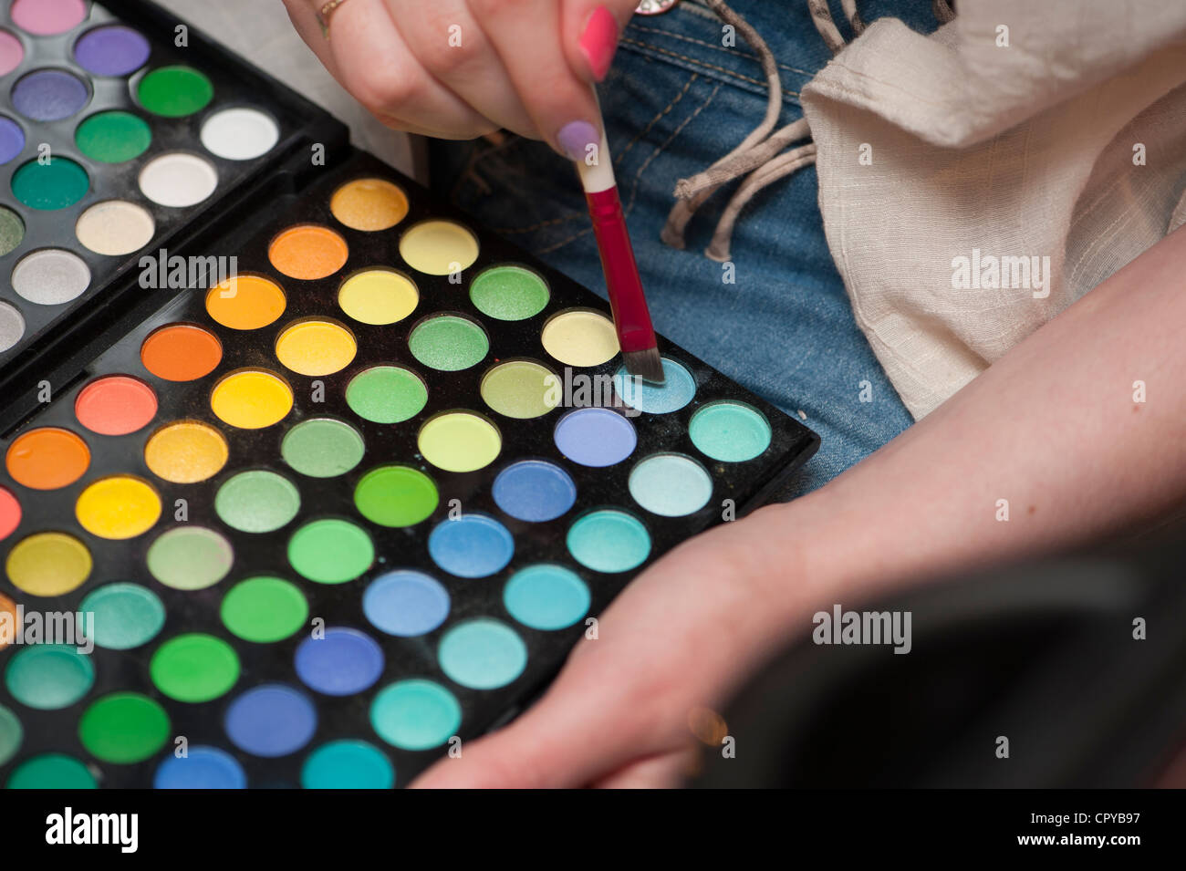 A young woman choosing the correct colour make up for a make-over session at a salon UK - Stock Image