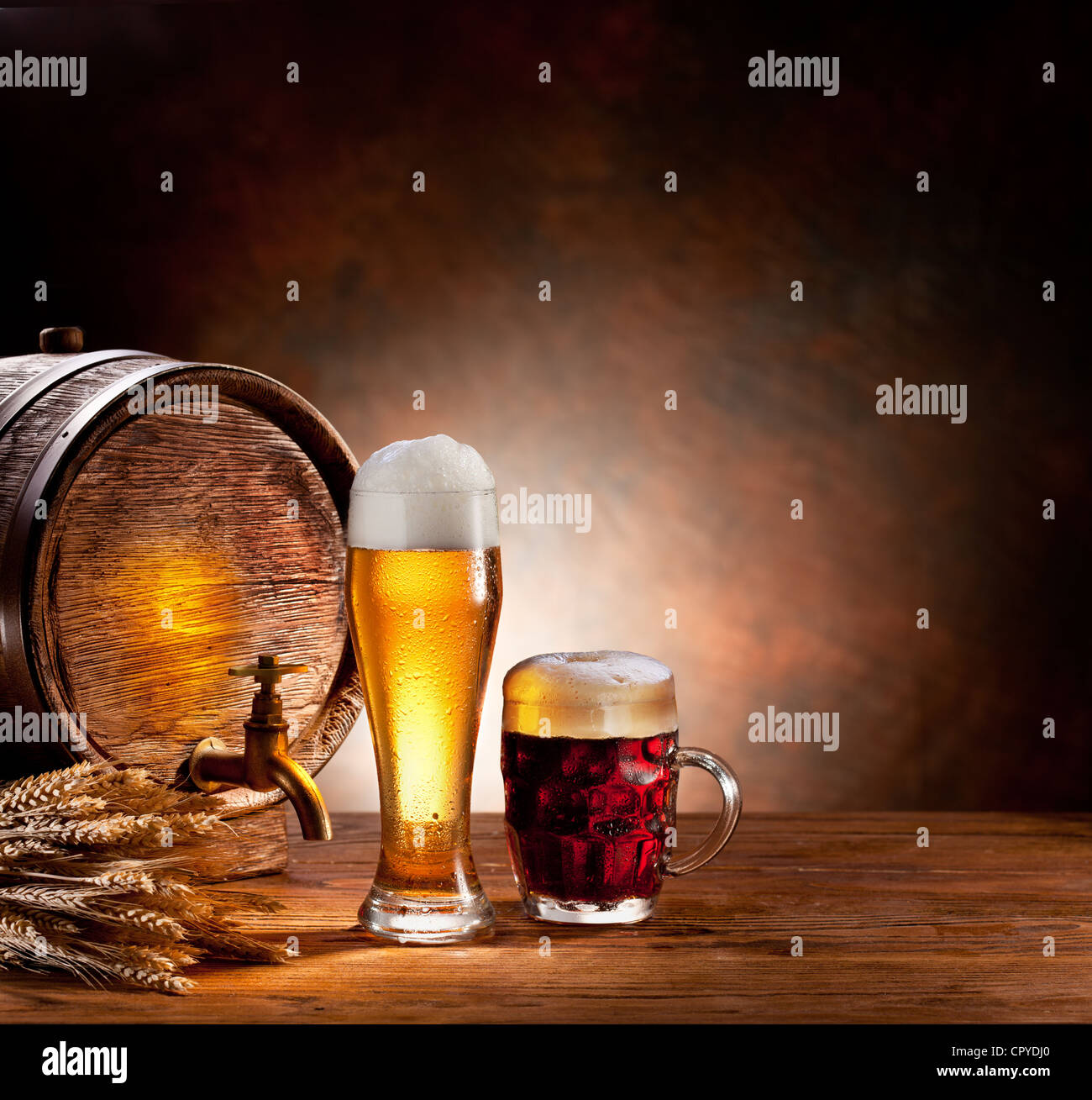 Beer barrel with beer glasses on a wooden table. The dark background. - Stock Image