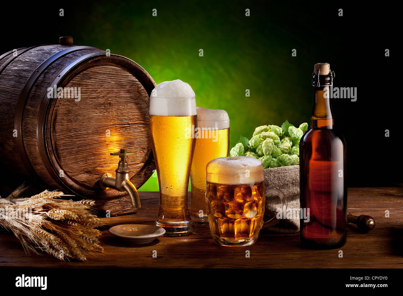 Beer barrel with beer glasses on a wooden table. The dark green background. - Stock Image