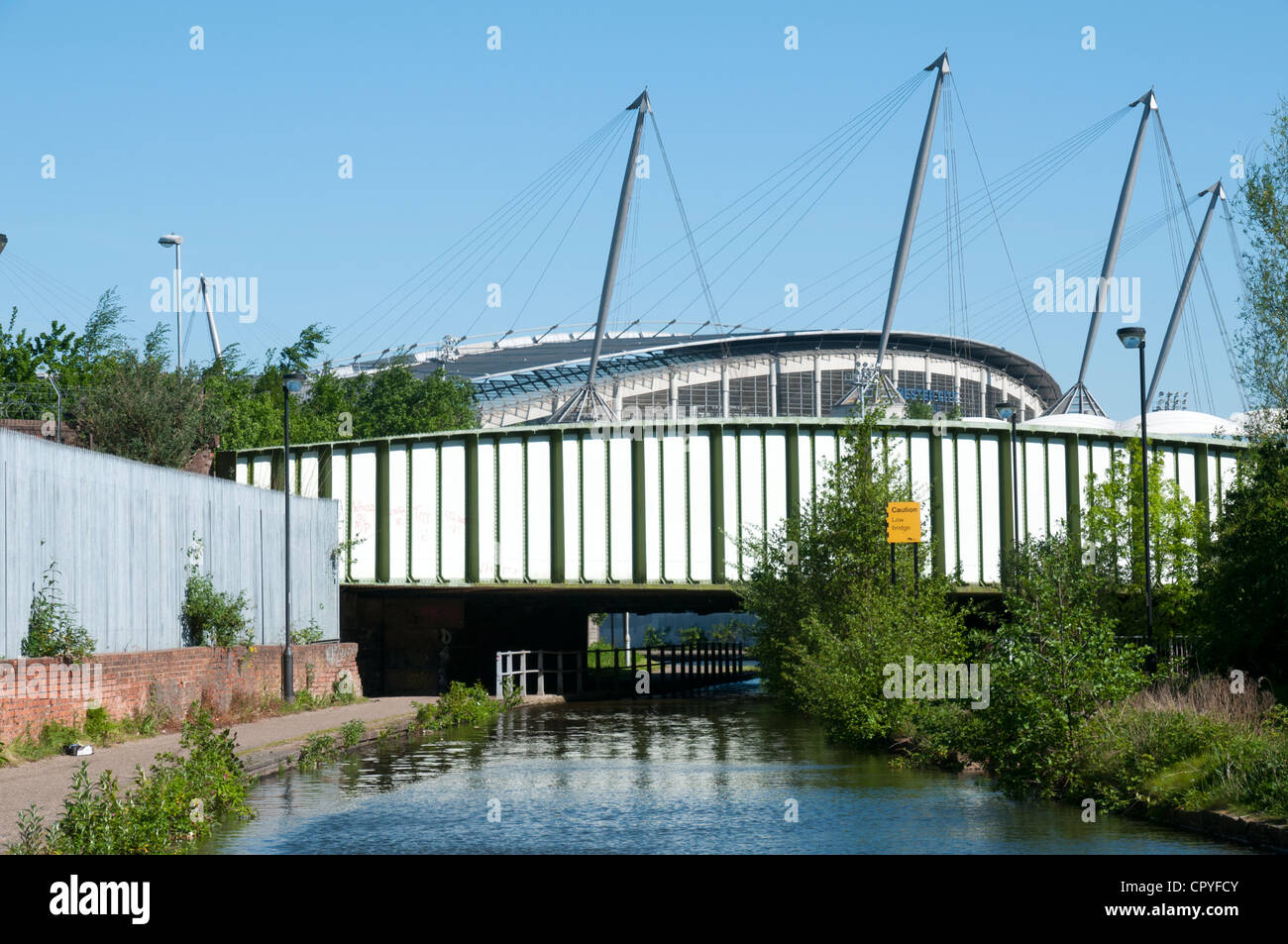 The Etihad Stadium and a railway bridge from the Ashton Canal, Ancoats, Manchester, England, UK - Stock Image