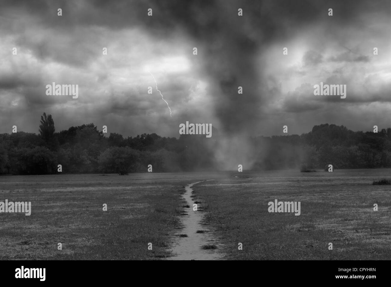 Tornado twister on the village road with lightning and dramatic sky - Stock Image