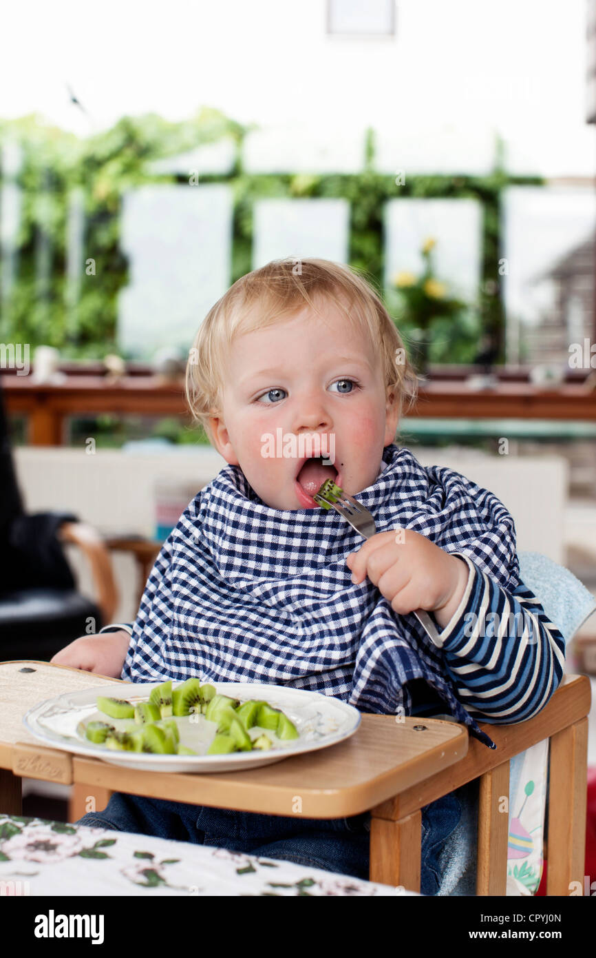 Young boy (15 months old) eating kiwi fruit with a fork
