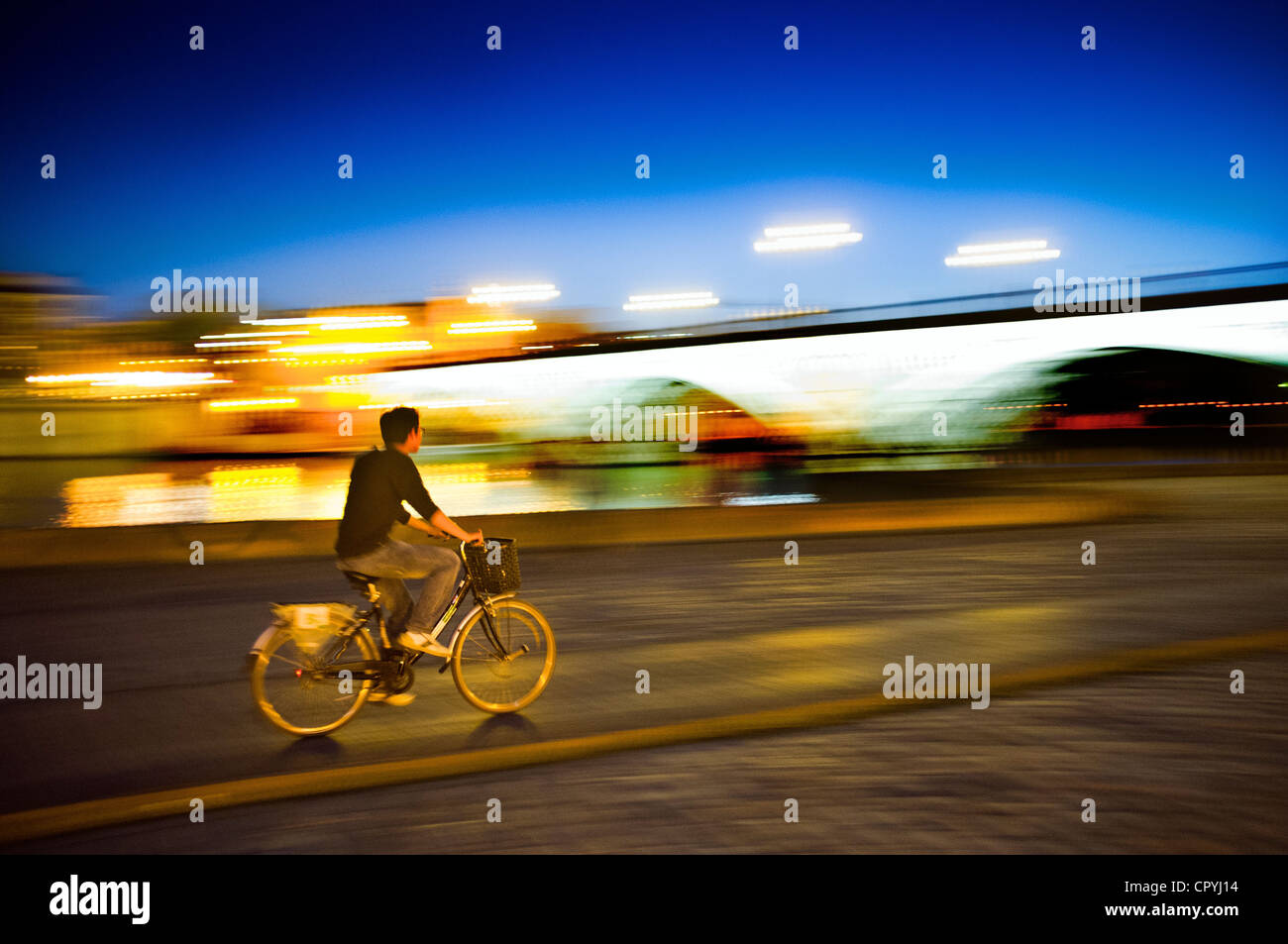 Panning shot of a cyclist by Tirana Bridge, Seville, Spain - Stock Image