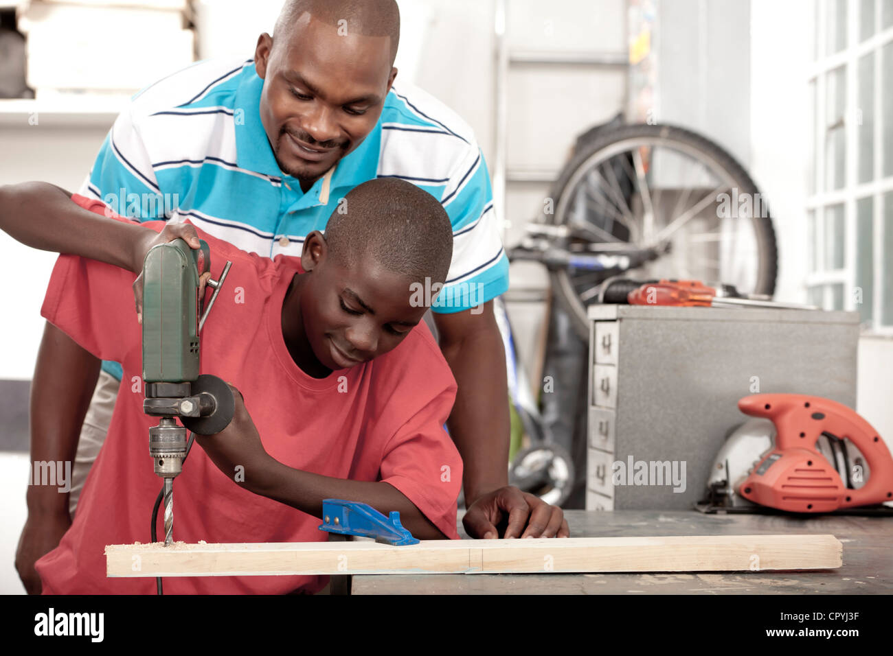 African Father and son using a drill in a workshop - Stock Image