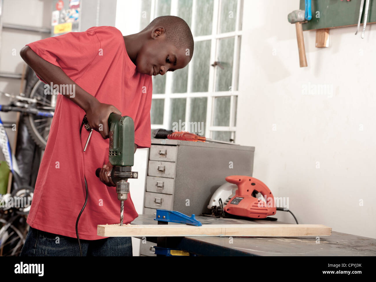 African child using drill in a workshop - Stock Image