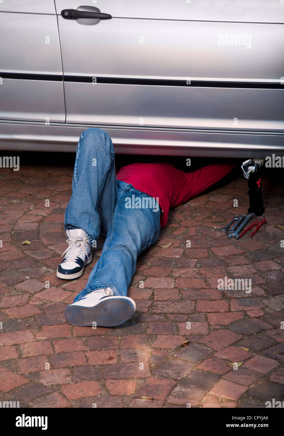 African man working on a car while lying underneath it - Stock Image