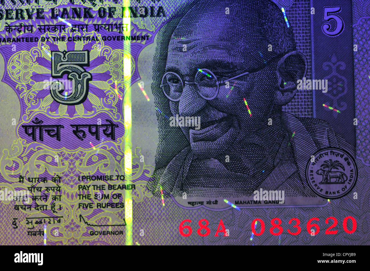 Banknote in ultraviolet light showing otherwise invisible security features. India, 5 Rupees - Stock Image